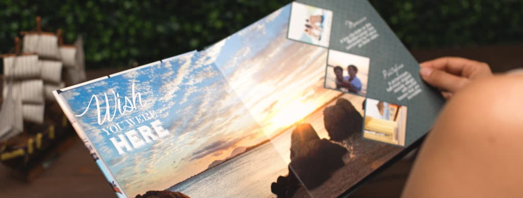 Woman going through printed photo book with travel memories